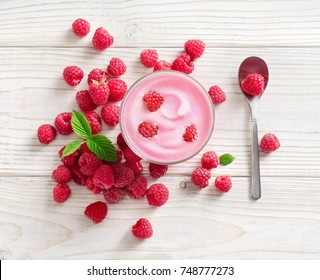 Yogurt with fresh raspberry on white wooden table. Fresh yogurt. Healthy food concept. High resolution product. Top view