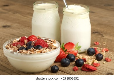 yogurt with fruit and müsli on wooden background
