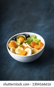 yogurt with fruits, grapes, physalis, bananas and blueberries, top view