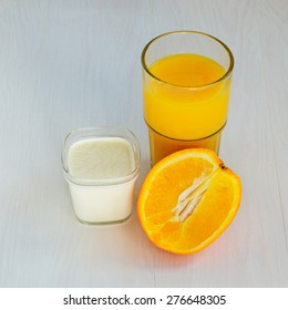 Yogurt in a glass cup and orange juice on a white background