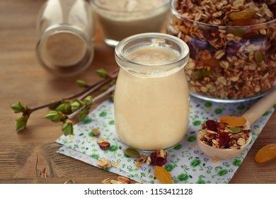 Yogurt in a glass jar and granola in the background
