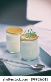 Yaourt dans un bocal de verre avec une cuillère. Aliments sains pour le petit-déjeuner, produits laitiers