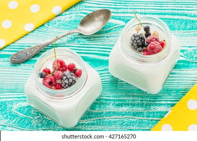 yogurt in glass jars, frozen berries, old spoon,  yellow napkin at white polka dots on turquoise colored wooden table, top view