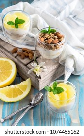 Yogurt with granola, almonds and grapefruit slices on old wooden background