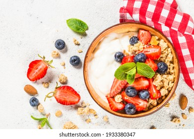 Yogurt granola with fresh berries on white stone table. Top view with copy space. Healthy food, snack or breakfast.