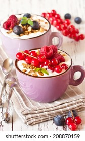 Yogurt with granola and fresh berries on an old wooden board.