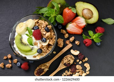 Yogurt with granola and fruits in glass on black granite stone table