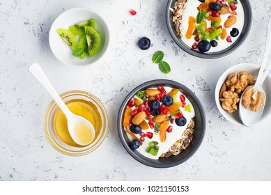 Yogurt, milk porridge, granola for breakfast with different berries, nuts and fruits: kiwi, pomegranate, dried apricots, blueberries, almonds and honey. Portionally. Top view Food concept