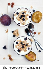 yogurt with muesli and berries in glasses from above