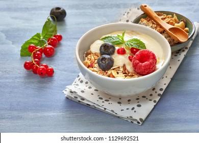 Yogurt with muesli and berries, healthy dessert on light blue background