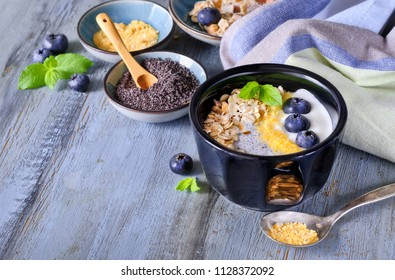 Yogurt with muesli, blueberries, poppy seeds, mint and crushed cornflakes served in black shiny bowl on rustic wooden table