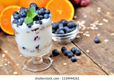 Yogurt with oatmeal, fresh blueberries and mint leaves and orange and grapes in background