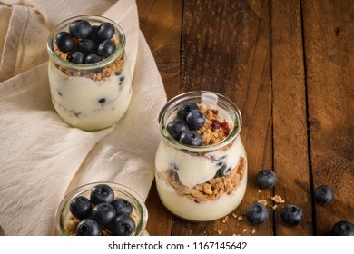 Yogurt parfait with blueberry and granola. Healthy breakfast concept served in mason jar with decorative spoons on wooden table.