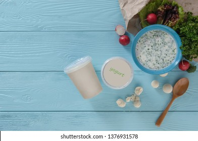 yogurt in a plastic container and greens with radishes on a blue wooden background, top view. healthy eating concept