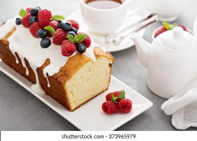 Yogurt pound cake for breakfast with glaze and fresh berries