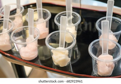 Yogurt sample and plastic spoon in transparent tasting cup on wooden black tray. Marketing promotion for new launched flavor of healthy product.