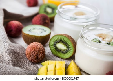Yogurt with tropical fruits on a wooden background. Tasty breakfast. Healthy eating.