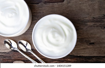 Yogurt white put in a glass put on a wooden background from top view.