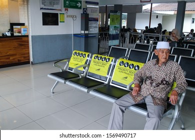 Yogya 8 Nov 2019 - An old man is sitting down on black aluminium priority seat that covered with a yellow cap during waiting train in a railway station
