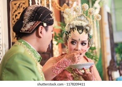 Yogyakarta 2 Oct 2018 - Beautiful couple is wearing traditional javanese wedding clothes while having their ceremonial and drink a cup of tea