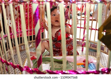 YOGYAKARTA 2011 - A girl is sitting down in the mat while covered with bamboo cage during cultural kid's ceremony called Tedak Siten in Yogyakarta