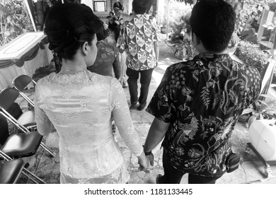 Yogyakarta 22 Oct 2012 - Black and white photo while two asian couple walking together and hold their hand each other, they are wearing batik and kebaya dress during wedding ceremony