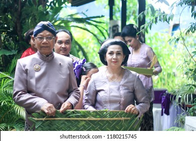 Yogyakarta 22 Oct 2012 - Happy parents are smiling and standing by during their daughter wedding, they wear beautiful grey-light purple javanese dress and nice hair do
