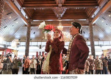 Yogyakarta 25 Sept 2011 - Happy javanese couple wearing red traditional kebaya dress and hold a fresh flower bouquet to be throuw to guest who attend their wedding party