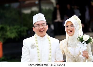 Yogyakarta 25 Sept 2011 - Happy marriage couple wearing white traditional wedding dress with jasmine necklace and hijab, bride holding the the white rose bouquet on her hand