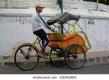 yogyakarta, di yogyakarta/indonesia - november 10, 2015: a becak driver on his vehicle on a road in yogyakarta looking out for clients