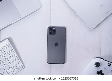 Yogyakarta, IDN - Oct 6, 2019 : iPhone 11 Pro Space Grey with, macbook,  gaming controller, mockup concept with office style background