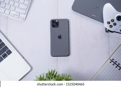 Yogyakarta, IDN - Oct 6, 2019 : Top view of Apple products tech mockup includes macbook, ipad , game controller, and new iPhone 11 Pro Space Grey