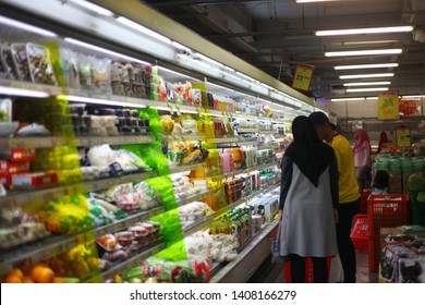 Yogyakarta, Indonesia - 05/26/2019 : Man wearing yellow shirt and women wearing jilbab standing in a supermarket. Shopping ahead of Eid al-Fitr