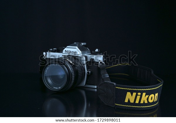 Yogyakarta, Indonesia - 12 May 2020: Nikon FM2 analog camera silver edition with strap and black background
