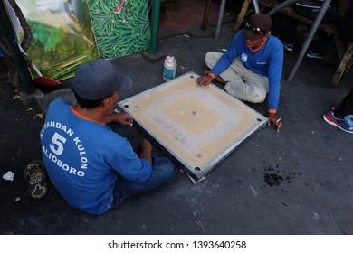 Yogyakarta Indonesia 19 August 2016 2 guys playing carom board at beringharjo traditional market