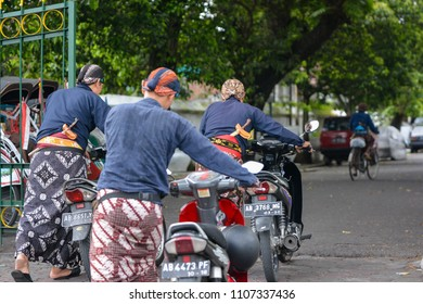 """YOGYAKARTA, INDONESIA - 2018: """"Abdi Dalem"""" or the sultan's servant was pushing a motorcycle out of the Yogyakarta palace"""