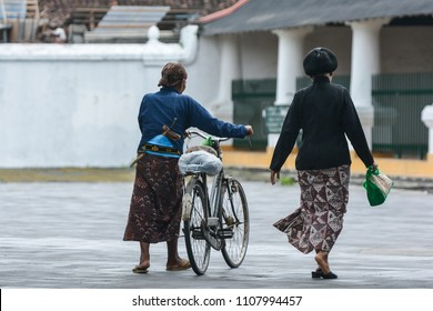 """YOGYAKARTA, INDONESIA - 2018: """"Abdi Dalem"""" or the sultan's servant was pushing a bycyle in the palace of Yogyakarta"""