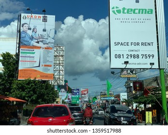 """""""Yogyakarta, Indonesia - 2019 March 2: Description"""" Drivers of motorized vehicles pass the Baliho Forest, on the road to Colombo, Yogyakarta. The number of billboards is due to the high need for promo"""
