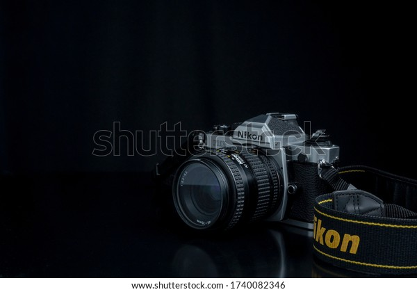 Yogyakarta, Indonesia- 24 May 2020: Nikon FM2 SLR analog camera close up view with strap and dark background