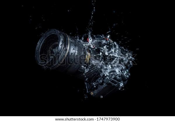 Yogyakarta, Indonesia - 30 May 2020: High speed shot of water splashing on Nikon D800 DSLR camera body with dark black background