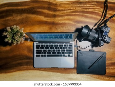 Yogyakarta, Indonesia - 9 Februari 2020: Top view of Apple Macbook air with pen tablet and digital camera on wooden table as Photographer tools symbol
