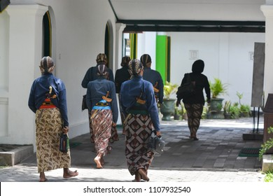 """YOGYAKARTA, INDONESIA - AUGUST 10 2017: The """"Abdi dalem"""" or servant of the sultan was chatting while walking in the palace of Yogyakarta"""