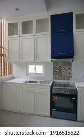 Yogyakarta, Indonesia - February 13 2021: Modern minimalist clean white kitchen set cabinet with blue accent colour.