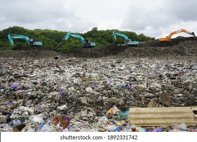 Yogyakarta, Indonesia - Jan 12th 2021 Scenery at TPST Piyungan a trash landfill. Scoop backhoe machines on duty with beautiful green hill on the background