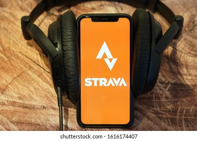 Yogyakarta, Indonesia - January 15, 2020; Strava Apple Store Application on a Brown Wooden Table with Black Headset Speaker