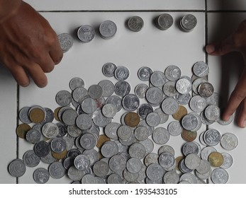 Yogyakarta Indonesia January 2021: Hand counting indonesian rupiah coin pile