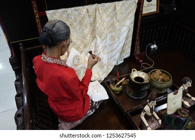 YOGYAKARTA, INDONESIA – July, 2 2018: Unidentified batik maker use watercolor to color on the fabric to make Batik. Batik-making is part of Indonesian culture and tourist attraction in Yogyakarta.