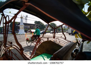 Yogyakarta / Indonesia - July 28, 2016 : Tugu Jogja the historical landmark framing from becak traditional transportation.