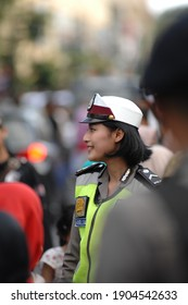 YOGYAKARTA, INDONESIA - JULY 8, 2017: Bokeh picture of a beautiful policewoman in the middle of a crowd maintaining security at a traditional carnival in Yogyakarta