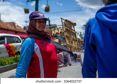 Yogyakarta, Indonesia - March 16, 2018: Smiling woman selling flutes on Malioboro Road in Yogyakarta.